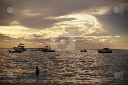 Boats at Sunset in Costa Rica stock photo, Costa Rica sunset with Boats and single bather in the Pacific Ocean by Scott Griessel