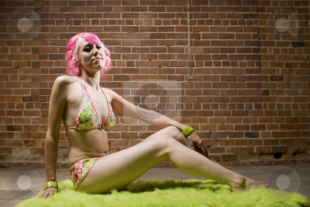 Pretty Woman with Pink Hair stock photo, Pretty Woman in a Bikini with Pink Hair on Green Rug by Scott Griessel