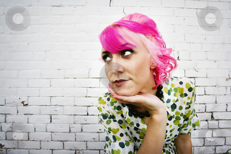 Woman in front of brick wall stock photo, Woman with pink hair in front of white painted brick wall by Scott Griessel
