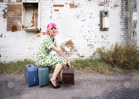 Woman with Pink Hair and a Small Siuitcases stock photo, Woman with pink hair wearing polka dot dress in alley with suitcases by Scott Griessel