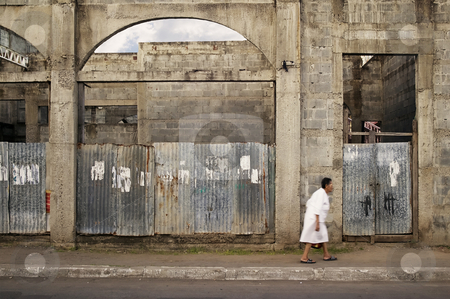 Woman on the Street in Granada Nicaragua stock photo, Old woman walks by a ruined building in Granada Nicaragua by Scott Griessel