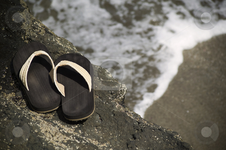Sandals by the shore stock photo, Sandlas on a rock with ocean wave in the background by Scott Griessel