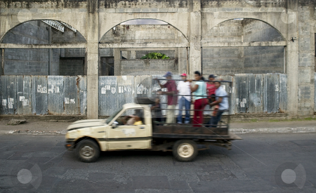 Truck Passby in Nicaragua stock photo, Truck full of people drives by abandoned building in Granada Nicaragua by Scott Griessel