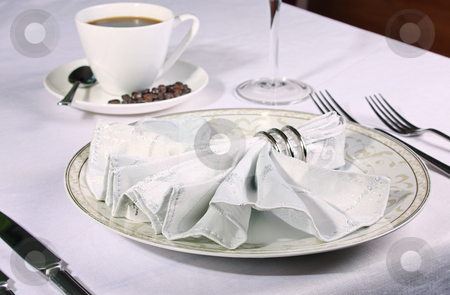 Elegant place setting with piping coffee in background stock photo, Elegant place setting with piping coffee in background and white fan napkin and ring by Mark Allchin