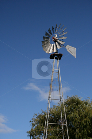 Windmill and Blue Sky stock photo, A vintage towering windmill set against a brilliant blue sky. by Betty Hansen