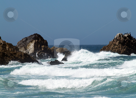 Waves breakers amidst rocks at sea shore stock photo, Waves breaking with rocks at the ocean shoreline by Jeff Cleveland