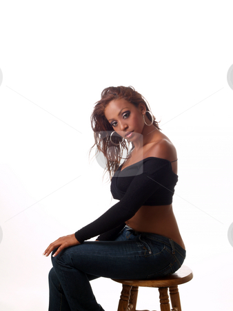Woman sitting on stool stock photo, Young woman in jeans and black sweater on stool by Jeff Cleveland