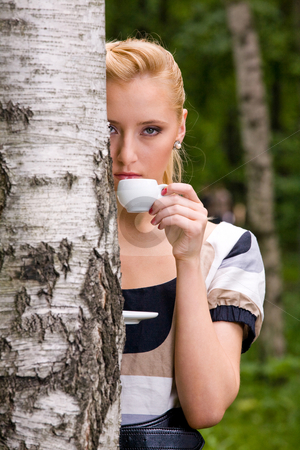 Beautiful young woman and coffee stock photo, Blond lovely young woman drinking cup coffee outside by Vitaly Sokolovskiy
