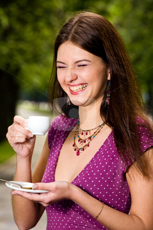 Beautiful young woman and coffee stock photo, Laughing lovely young woman drinking coffee outside by Vitaly Sokolovskiy