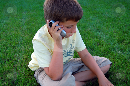 Preteen boy talking on cell phone stock photo,  by Heather Shelley