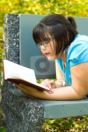 Story Book stock photo, A young girl reading a story book outside by Richard Nelson