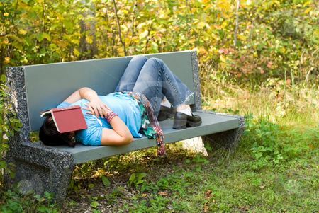 Sleeping Outside stock photo, A young girl sleeping on a park bench outside by Richard Nelson