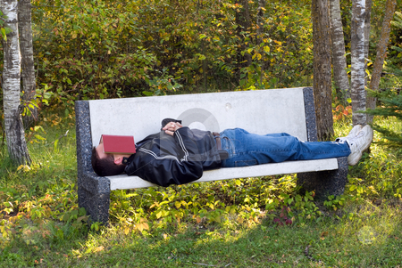 Man Sleeping Outside stock photo, A young man sleeping on a park bench with a book over his face by Richard Nelson