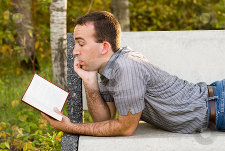 Man Reading A Novel stock photo, A young man in a park reading a novel by Richard Nelson