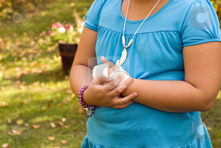 Sore Wrist stock photo, Young girl holding her sore wrist with a sloppy bandage on it by Richard Nelson