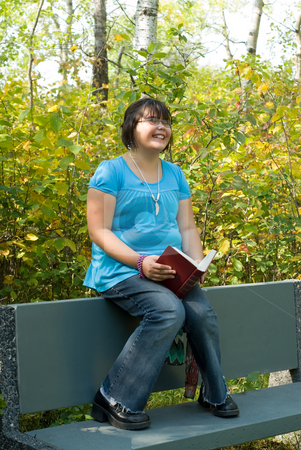 Funny Book stock photo, A nine year old girl reading a funny book outside by Richard Nelson