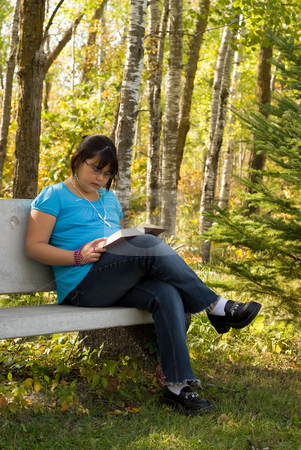 Girl Reading stock photo, A young girl sitting in the park reading a book by Richard Nelson