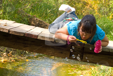 Having Fun stock photo, A nine year old girl lying on a wooden bridge blowing bubbles by Richard Nelson