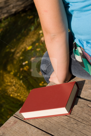Solitude stock photo, A young girl sitting on a dock with her book by Richard Nelson