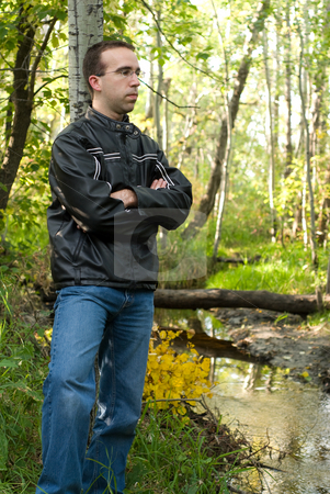 Man Relaxing By A Stream stock photo, A young man leaning against a tree and relaxing by a stream by Richard Nelson