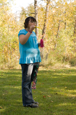 Blowing Bubbles stock photo, Nine year old girl about to blow bubbles in the park by Richard Nelson