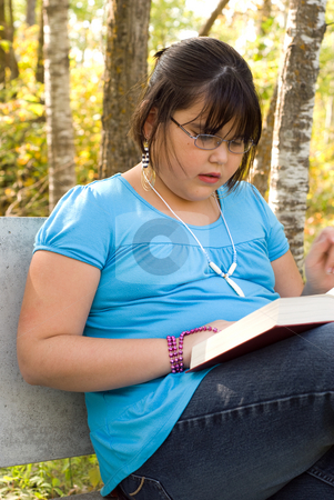 Reading Outside stock photo, A nine year old girl reading a book outside by Richard Nelson