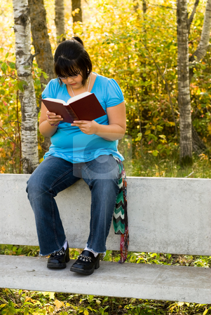Relaxing stock photo, A nine year old girl reading a book in the park by Richard Nelson