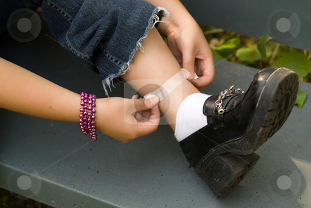 Injury stock photo, A young girl putting a bandaid on her leg by Richard Nelson