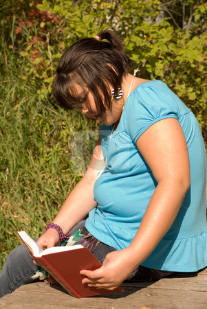Girl Reading A Book stock photo, A nine year old girl sitting in the park reading by Richard Nelson