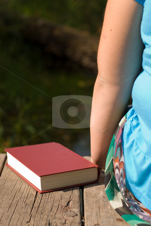 Peace and Relaxation stock photo, Child and book sitting on a wooden dock outside by Richard Nelson