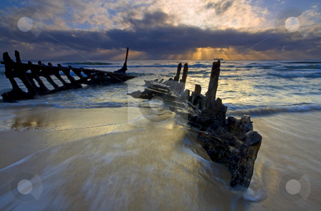 Body of shipwrecked boat stock photo, The shipwreck of the S. S. Dicky on a Sunshine Coast Beach in Australia. A 40 ton steamer ran aground in 1893. The sea has gradually carved away at it after over 110 years of the waves washing over it. A glorious sunrise helped illuminate it as the tides began to come in. by Mike Dawson