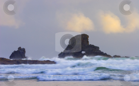 Consumed by the Sea stock photo, A arch carved in this seastack off the ORegon near Ecola State Park engulfed by the rising tides. by Mike Dawson