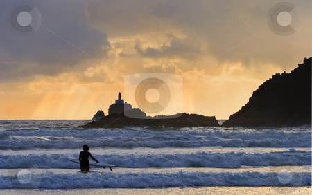 Surfer trekking into ocean stock photo, A lone surfer watches the surf rise as heavenly rays bathe the Tillamook Rock Lighthouse in the distance. by Mike Dawson