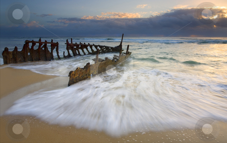 Swept Ashore stock photo, The shipwreck of the S. S. Dicky on a Sunshine Coast Beach in Australia. A 40 ton steamer ran aground in 1893. The sea has gradually carved away at it after over 110 years of the waves washing over it. A glorious sunrise helped illuminate it as the tides began to come in. by Mike Dawson