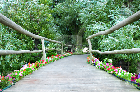 Wooden decorative bridge stock photo, Wooden bridge with rails and flowers between green trees by Julija Sapic