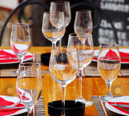 Table appointments stock photo, Wineglasses and plates on table in restaurant by Julija Sapic