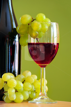 Wine with grape bunch stock photo, Red wine glass with grape and bottle over green by Julija Sapic
