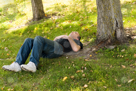 Dreaming Under A Tree stock photo, Man lying under a tree in the shade by Richard Nelson