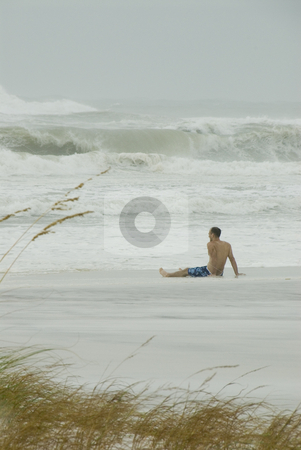 Gustav Lone Watcher Portrait stock photo, PENSACOLA - SEP 1: A lone spectator watches the surf pound during Hurricane Gustav on September 1, 2008.  Gustav claimed the lives of over 130 people. by A Cotton Photo