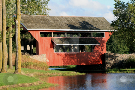 1800's Red Covered Bridge  stock photo, Red wooden 1800's era covered bridge set in a park like setting. Surrounded by green grass, mature trees, stonework and a beautiful lake. by Betty Hansen