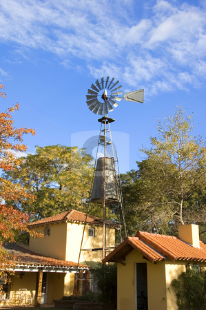 Farmhouse Windmill stock photo, A colonial style farmhouse with active windmill by Lee Torrens