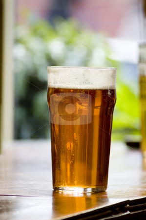Beer Pub stock photo, Typical pub seen with a beer in the foreground by Lee Torrens
