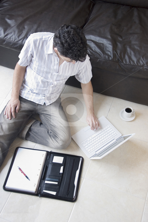 Man Telecommuting stock photo, A young professional businessman working from home with laptop and a coffee by Lee Torrens