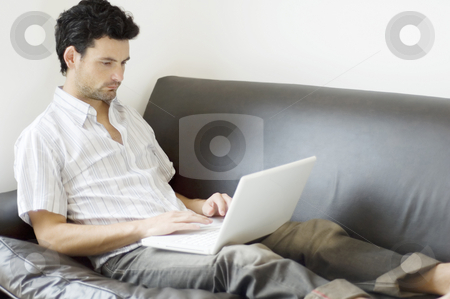 Man Working from Home stock photo, A young professional man working from home, relaxed on the sofa. by Lee Torrens