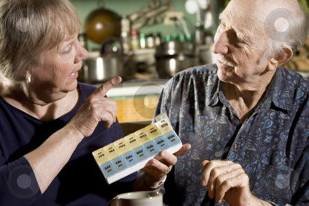 Portrait of Senior Couple with Pill Case stock photo, Portrait of Senior Couple Discussing Medications by Scott Griessel