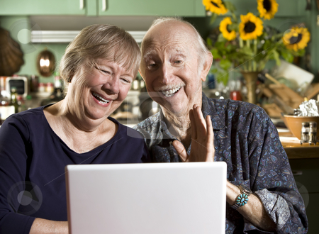 Smiling Senior Couple with a Laptop Computer stock photo, Smiling Senior Couple in their Dining Room with a Laptop Computer by Scott Griessel