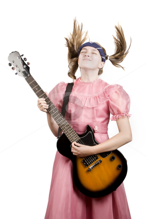 Young Girl with a Rock GuitarPlaying Headbanger Music stock photo, Young girl in a pink dress head-banging with an electric rock guitar by Scott Griessel