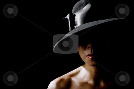 Woman in shadow wearing a black hat stock photo, Mysterious woman in shadows wearing  vintage black hat by Scott Griessel