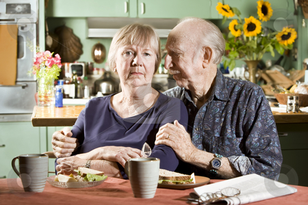 Portrait of Worried Senior Couple stock photo, Portrait of Worried Senior Couple in their Dining Room by Scott Griessel