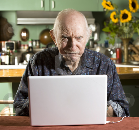 Grumpy Senior Man with a Laptop Computer stock photo, Grumpy Senior in Dining Room with a Laptop Computer by Scott Griessel